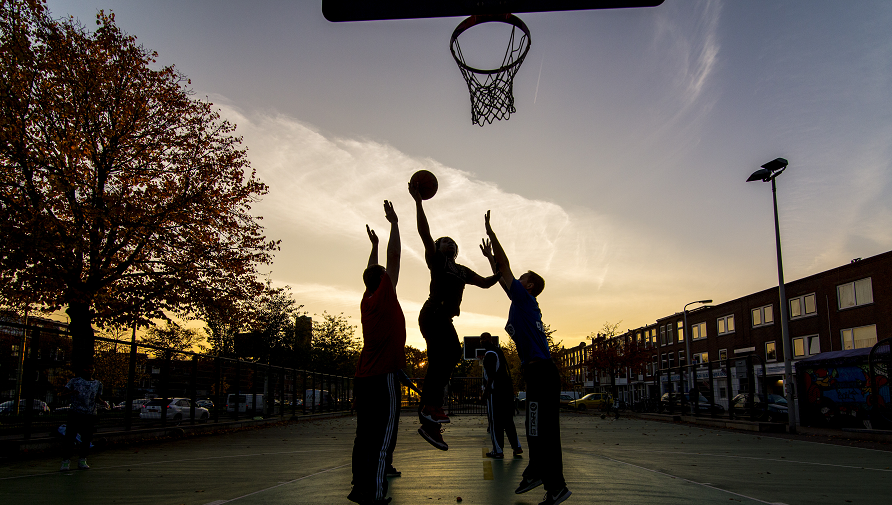 Three young people playing basketball
